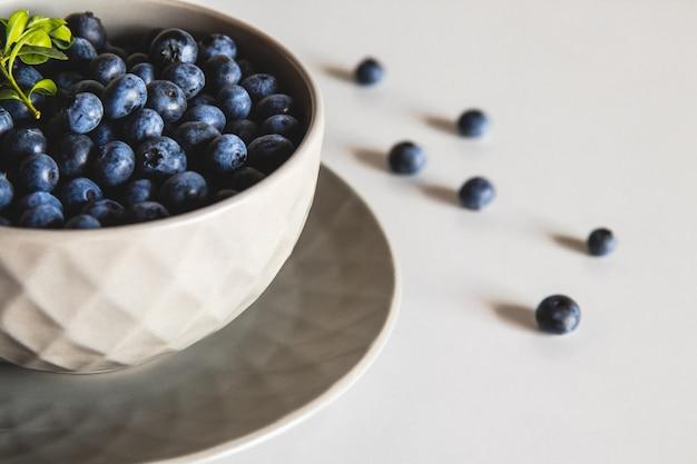 白いテーブルで隔離のボウルのブルーベリー。健康食品、健康