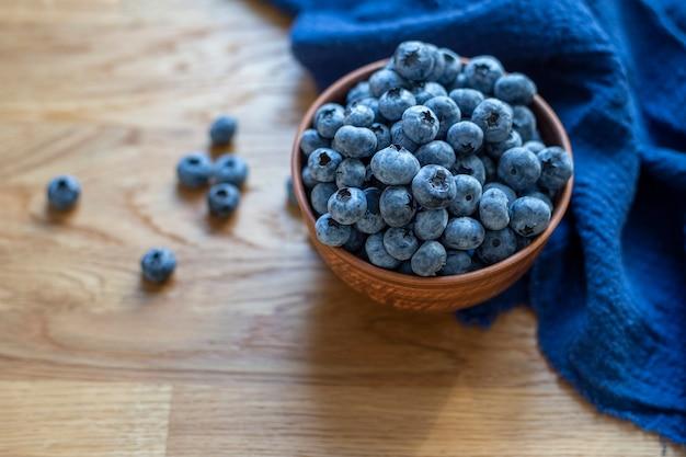 나무 배경에 파란색 수건이 있는 점토 그릇에 블루베리가 닫힙니다.