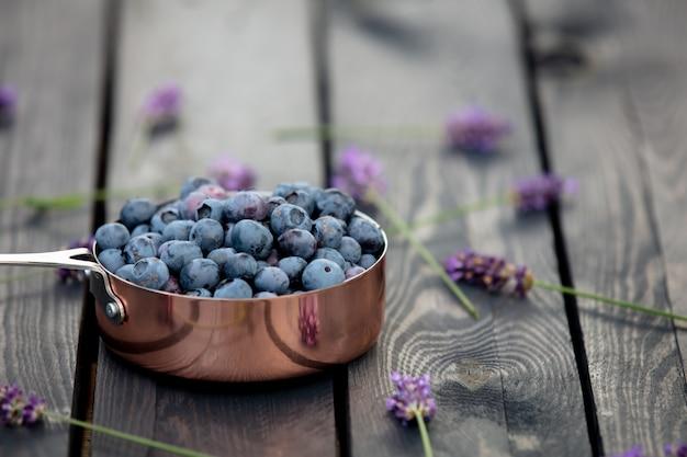 庭の木製のテーブルの周りの金属鍋とラベンダーの花のブルーベリー