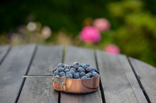 Черника в металлическом горшке на деревянном столе в саду