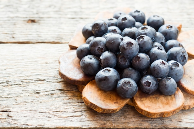 Blueberries on old wooden dishes, space for text