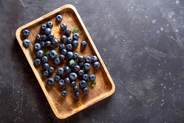 어두운 회색 테이블에 나무 접시에 블루 베리