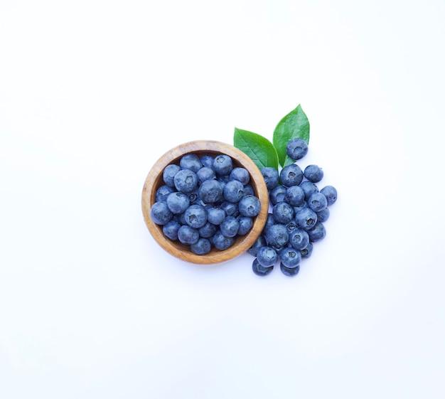 그릇 흰색 배경에 블루베리 일부 열매와 상위 뷰 주위에 녹색 잎
