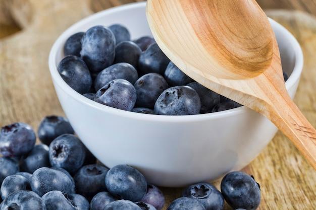 소박한 나무 숟가락으로 흰 그릇, 여름, 잘 익은 맛있는 딸기 클로즈업 테이블에 블루 베리