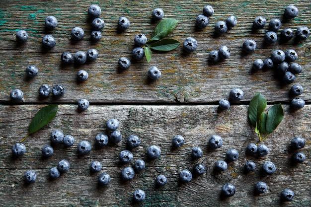 ヴィンテージの木製の背景の上面図のブルーベリー、暗いテーブルのモックアップの健康食品、ヴィンテージの素朴なカントリーボードのスムージーのベリー、新鮮なビルベリー