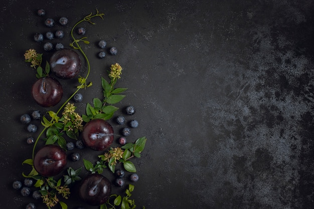 Blueberries and plums copy space