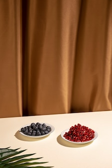 Blueberries and pomegranate seeds on plate with palm leaf over table against brown curtain