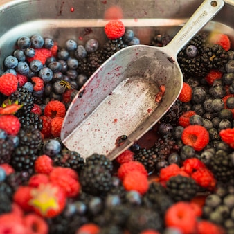 Blueberries; raspberries; blackberries in the container with spoon