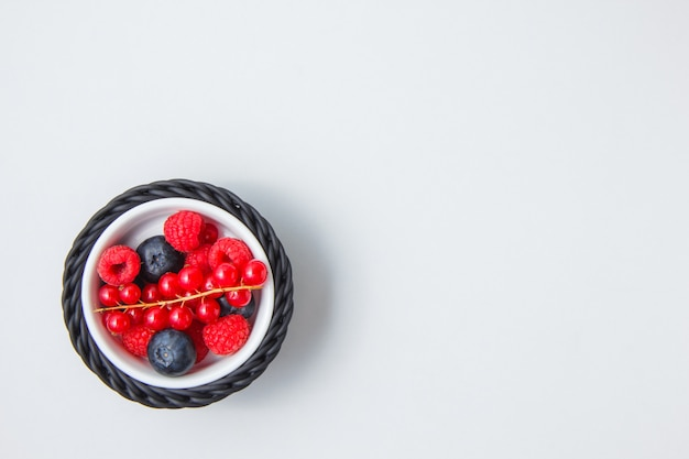 Blueberries and raspberries in a bowl with redcurrant top view
