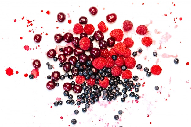 Blueberries, raspberries and cherries with drops of juice on white