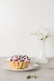 Blueberries tart on white ceramic plate with vase