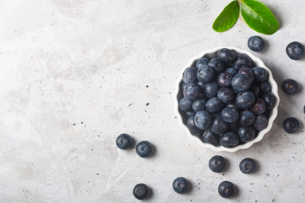 Blueberries in a white bowl with a leaf on a concrete background