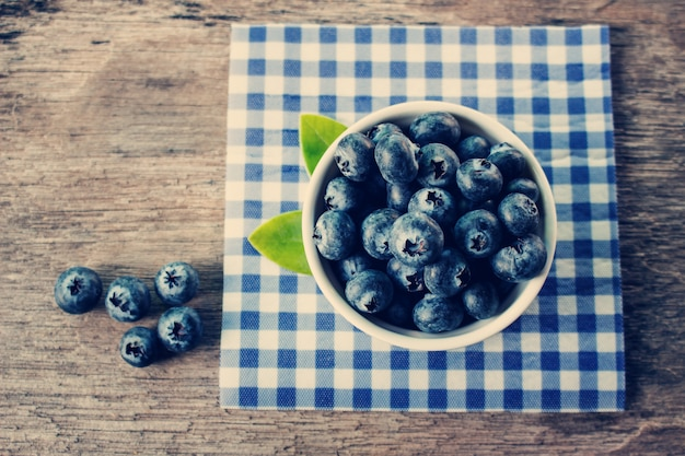 Blueberries in a white bowl on a wooden table Premium Photo