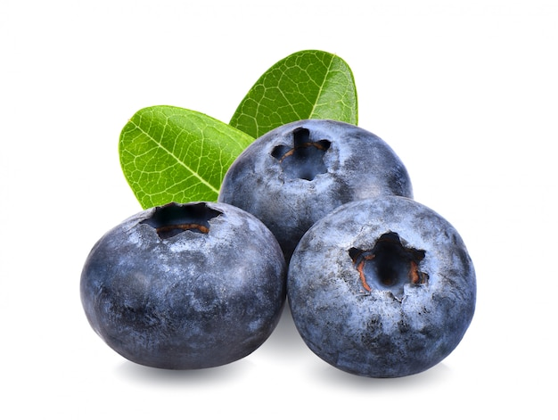 Blueberries with green leaves closeup, isolated on white surface