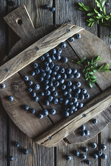 Blueberries on a wood board, wooden background closeup.