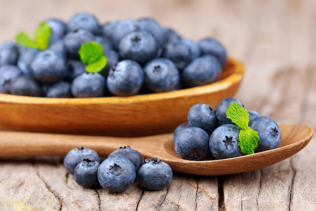 Blueberries in a wood bowl on a wooden table