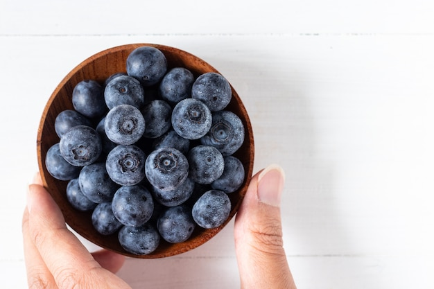Blueberries in a wooden bowl on white table