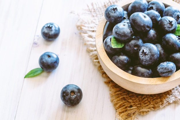 Blueberries in wooden bowl on wooden background
