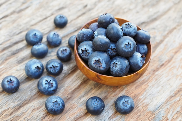 Blueberries in wooden bowls on old wooden table background