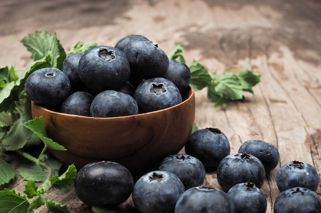 Blueberries in wooden bowls on old wooden table. rustic style