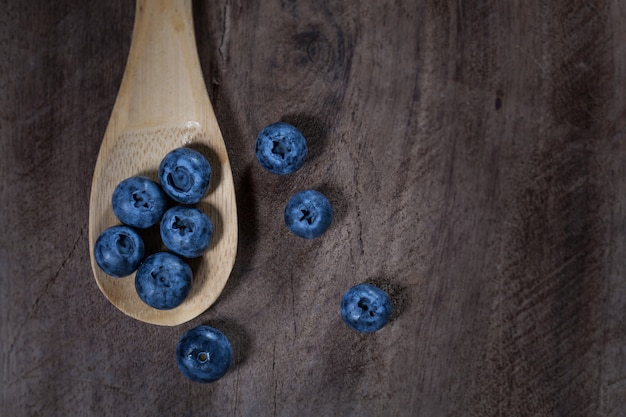Blueberries in a wooden spoon placed on a wooden table, taken from above.