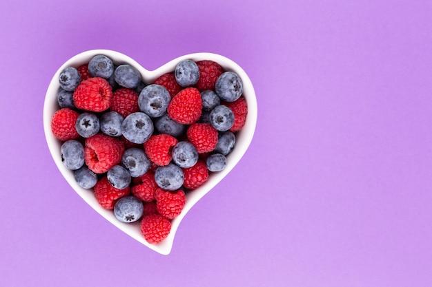 블루 베리와 라스베리, 도자기 그릇에 심장 모양의 접시에 과일