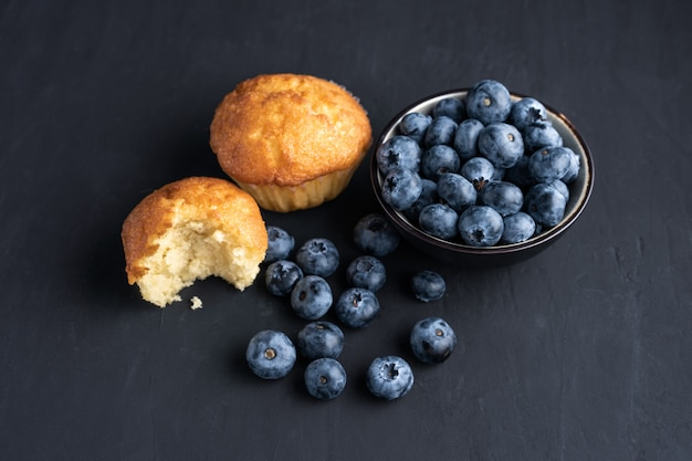 Blueberry antioxidant organic superfood in ceramic bowl and sweet muffin  for healthy eating and dieting nutrition top view on dark black