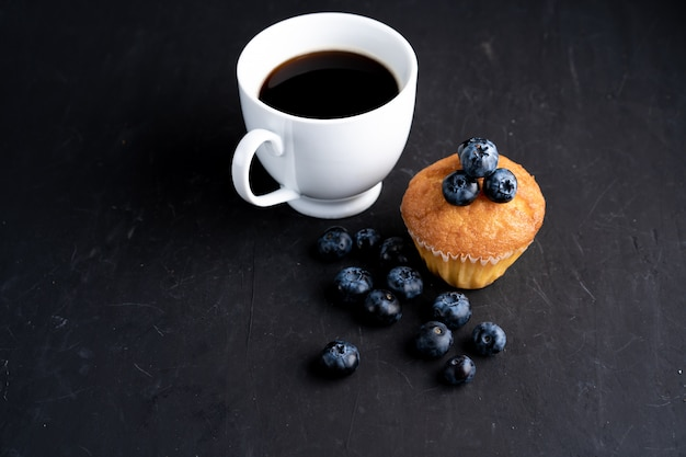 Blueberry antioxidant organic superfood and sweet muffin with cup of coffe  for healthy eating and dieting nutrition top view on dark black