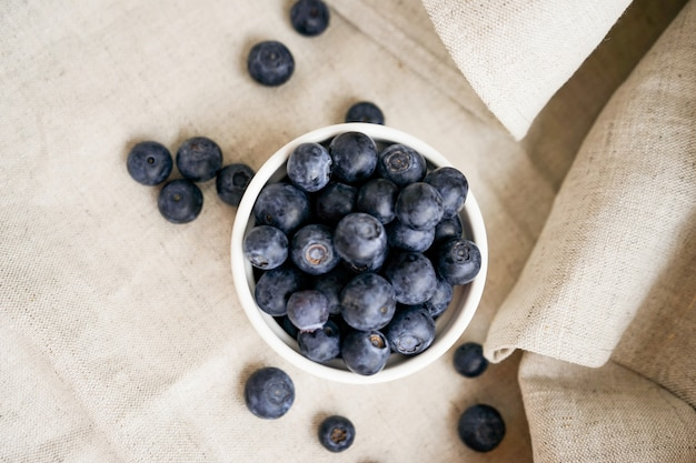 リネンクラフト生地に散乱したベリーと白い土鍋にブルーベリーの果実