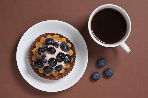 ブルーベリーのケーキと茶色のテーブルの上のコーヒー