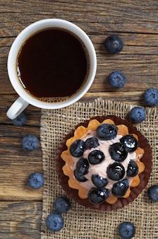 ブルーベリーケーキと木製のテーブルの上のコーヒー