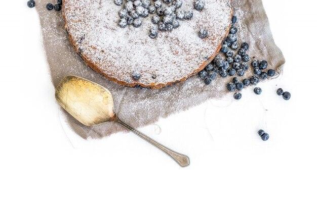 新鮮なブルーベリーと白い表面にベージュの生地に砂糖の粉でブルーベリーケーキ