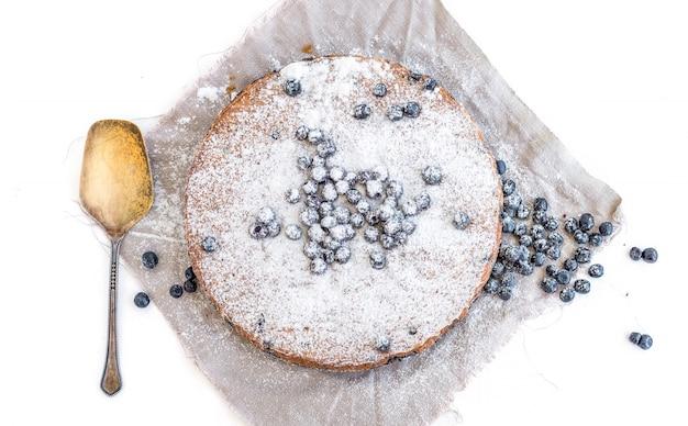 新鮮なブルーベリーと砂糖の粉をベージュの生地にブルーベリーケーキ