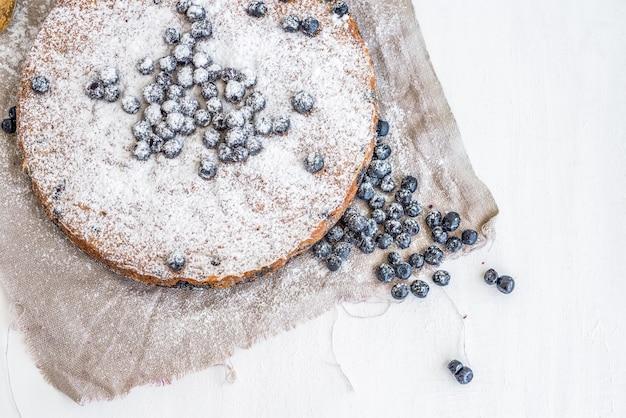 新鮮なブルーベリーと白い表面にベージュの布の上の粉砂糖とブルーベリーケーキ
