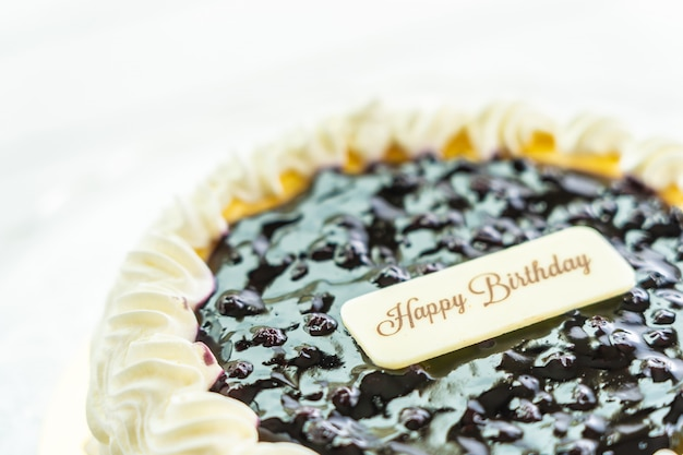 Blueberry cheese cake with happy birthday sign on top
