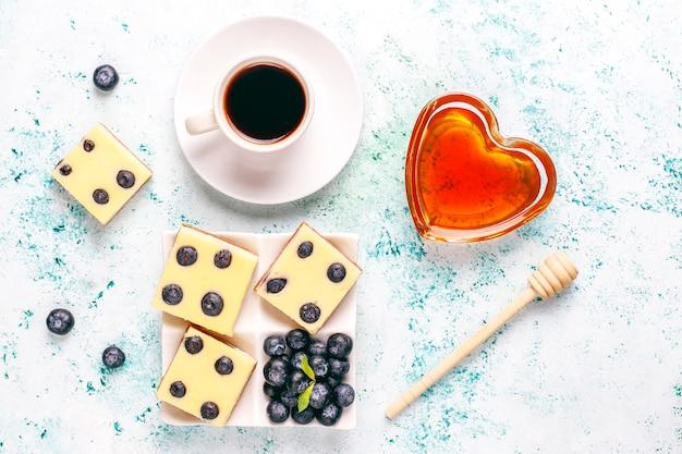 蜂蜜と新鮮なベリーのブルーベリーチーズケーキバー。