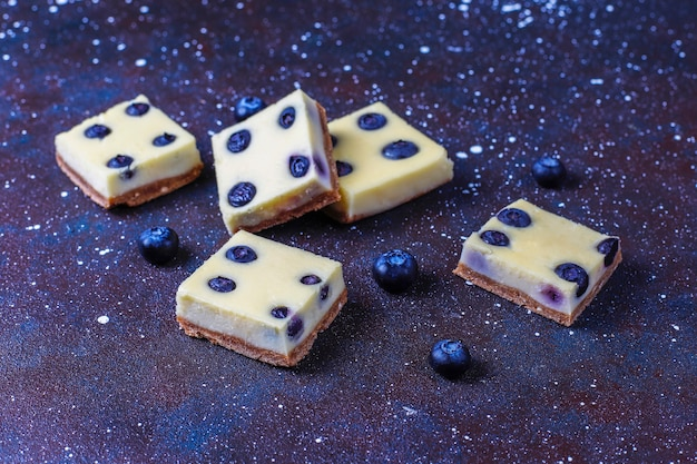 Barrette di cheesecake ai mirtilli con miele e frutti di bosco freschi.
