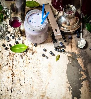 ブルーベリーカクテルとミルクスムージー。古い素朴なテーブルの上。