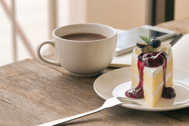 Blueberry cream cake on wood table with coffee or hot cacao.
