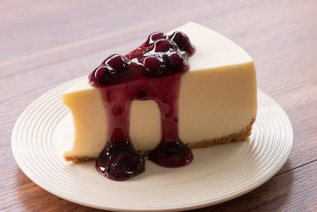 木製テーブルの上の白い皿にブルーベリークリームチーズケーキ