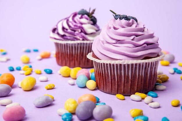 ライラックの背景にブルーベリーのカップケーキとカラフルなキャンディー