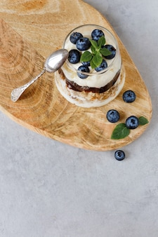 Blueberry dessert with curd cream and granola topping basil leaves. blueberry jam. top view.