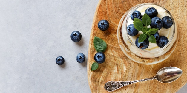 Blueberry dessert with curd cream and granola topping basil leaves on wooden stand. blueberry jam. top view.