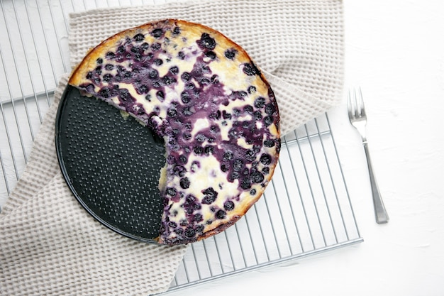 흰색 배경에 있는 블루베리 홈메이드 파이와 복사 공간이 있는 금속 베이스 탑 뷰. 맛있는 신선한 따뜻한 케이크를 닫습니다. 신선한 블루베리 파이. 맛있는 블루베리를 곁들인 비타민 오믈렛