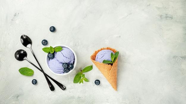 민트와 블루 베리 아이스크림 콘은 회색 표면에 나뭇잎. 평면도, 복사 공간