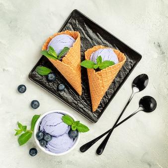 Черничное мороженое в вафельных рожках с ягодами и листьями мяты. вид сверху.