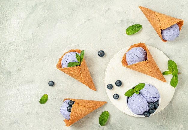 Вафельные рожки мороженого черники на конкретном сером фоне. плоская планировка, копия пространства.