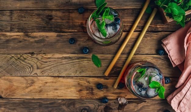 素朴な木製の背景に背の高いグラスにミントとブルーベリーアイスモヒート。