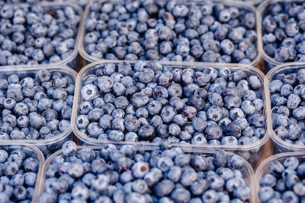 販売ファーマーズマーケットのためのプラスチックの透明な容器の箱のブルーベリー新鮮なベリー。セレクティブフォーカス