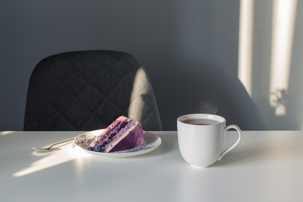 Blueberry lavender cheesecake on  plate and  cup of tea on white table